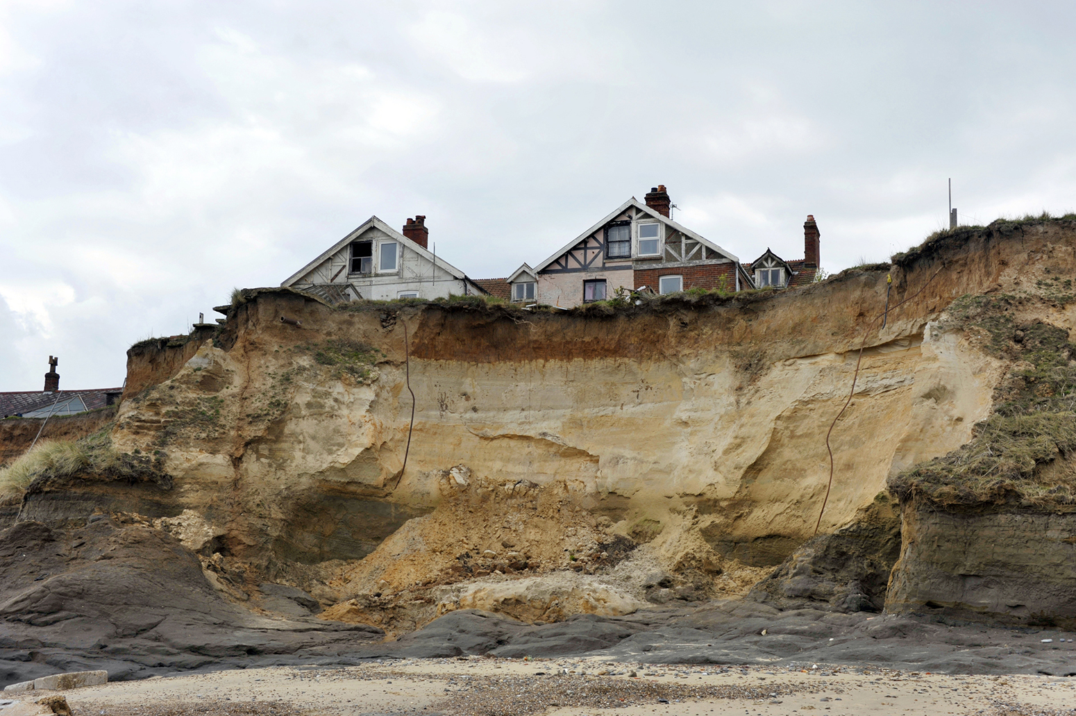 Homes in danger on the cliff edge at Happisburgh, Norfolk, UK