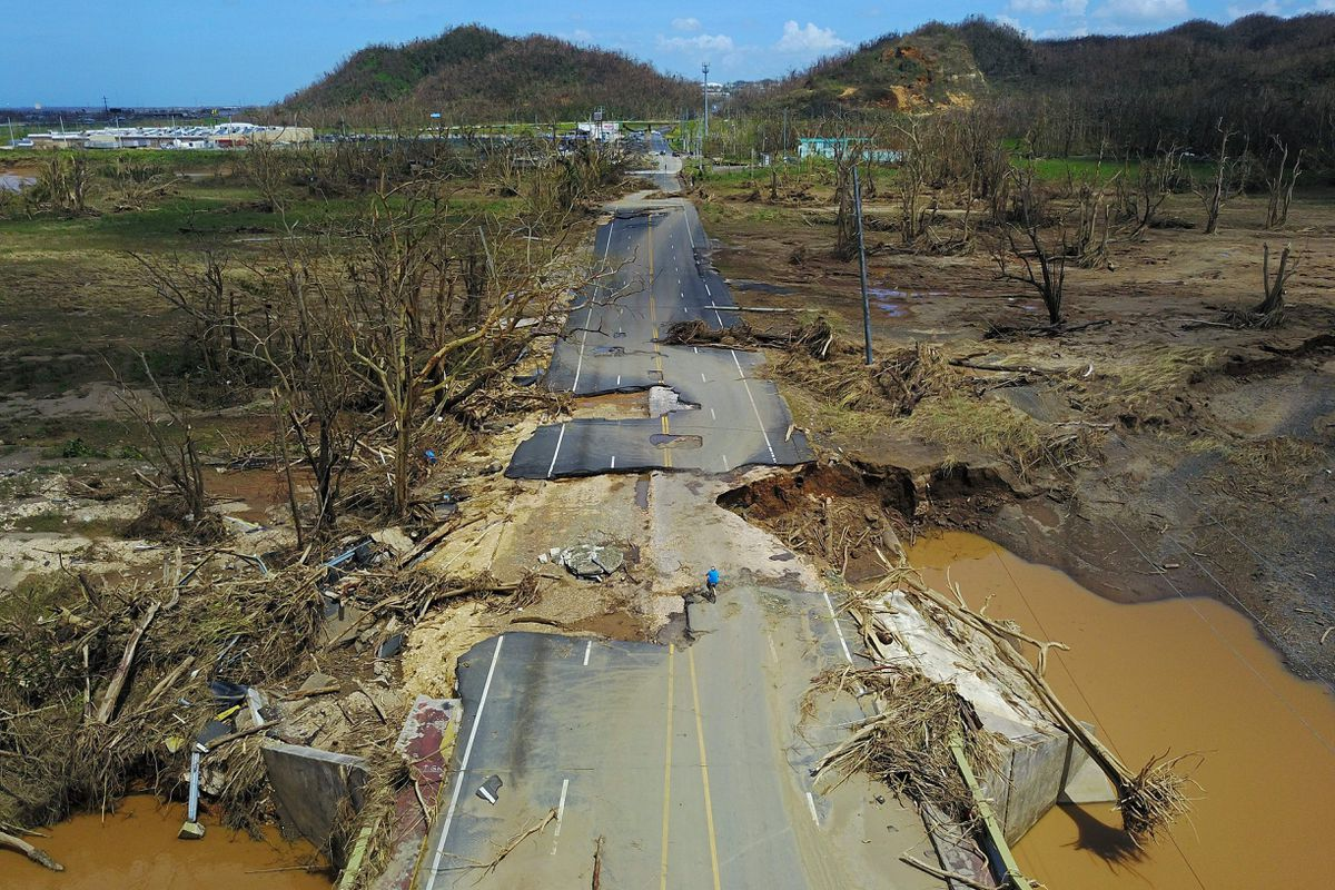 A man rides his bicycle through a damaged road in Toa Alta, west of San Juan, Puerto Rico, on September 24, 2017 following the passage of Hurricane Maria.