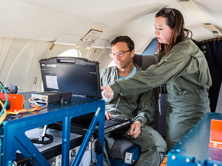 NASA Goddard's Peter Pantina, left, and Langley's Laura Judd make final checks before a flight.