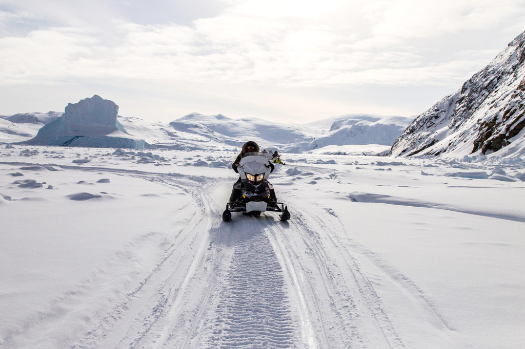 Ski-doo rider traverses a fjord on Baffin Island, Nunavut, Canada. Credit: Russell Millner / Alamy Stock Photo. MG3J49