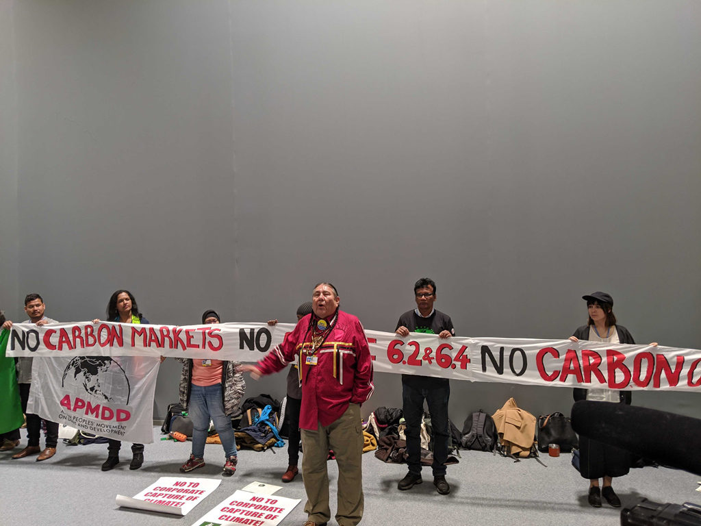 "Protestors at COP25 Madrid stand in front of a banner saying ""No Carbon Markets, No article 6.2 and 6.4"