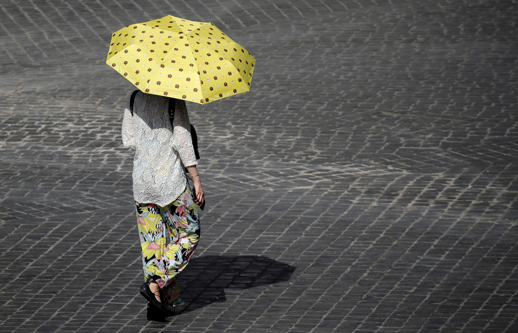 A woman shelters from the sun in downtown Rome as a heatwave hits Italy.