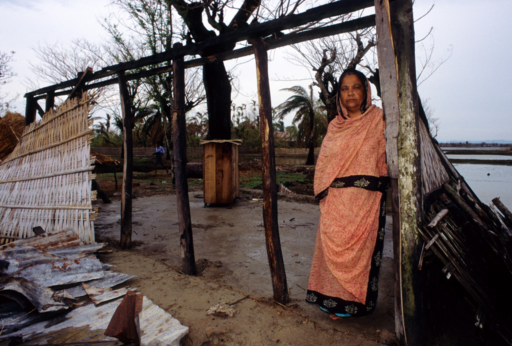 A-woman-stands-at-the-wreckage-of-her-home,-in-Banshkhali-Bangladesh