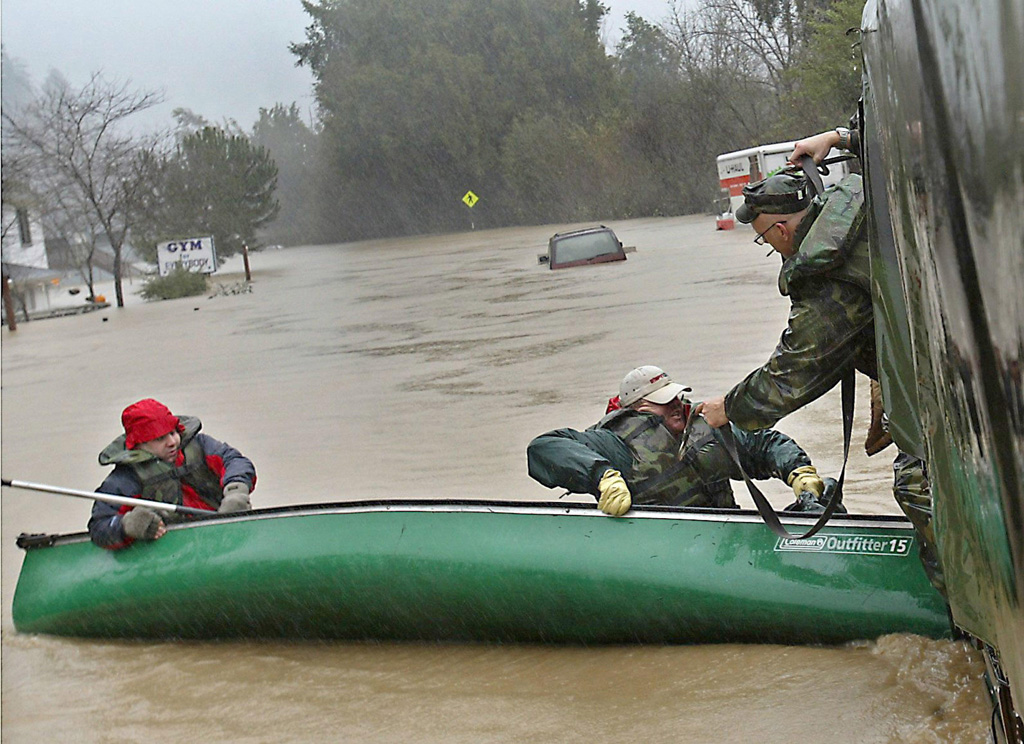 Two-men-are-rescued-by-the-National-Guard-after-their-canoe-tips-over-in-the-flooded-streets-of-Guernville-California