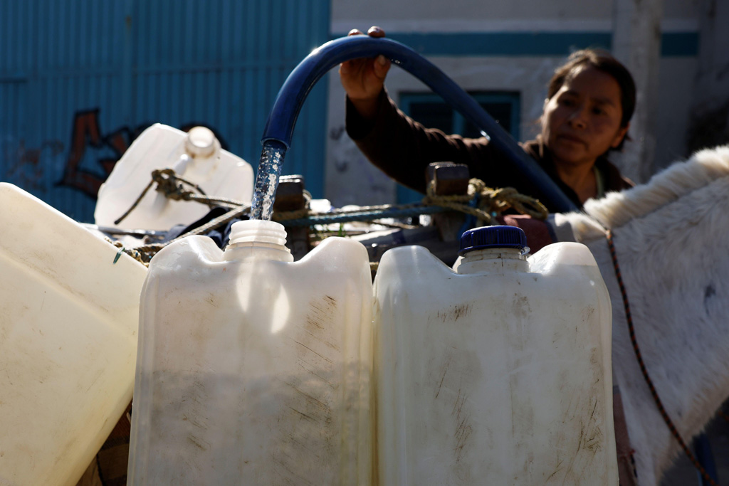A lady fills tanks with water for her family as as drought takes hold of Mexico City
