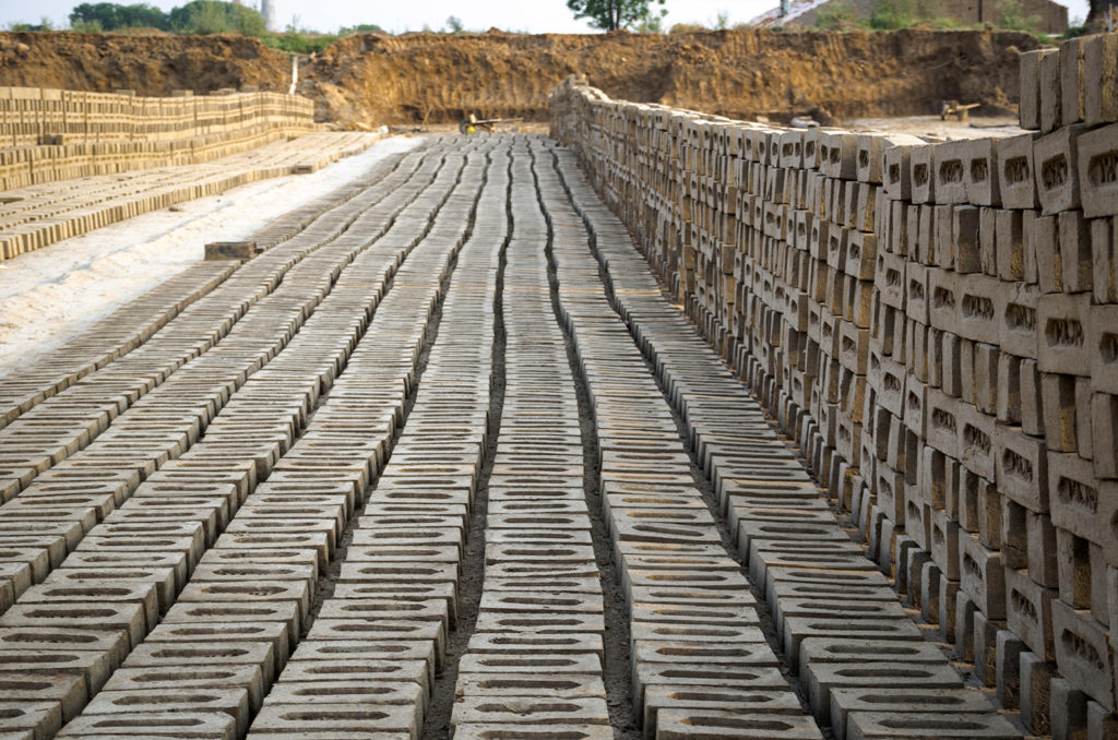 Bricks lined up to dry at a brick manufacturing facility in Amritsar, Punjab, India. Credit: GURPREET SINGH / Alamy Stock Photo. JMWXEX