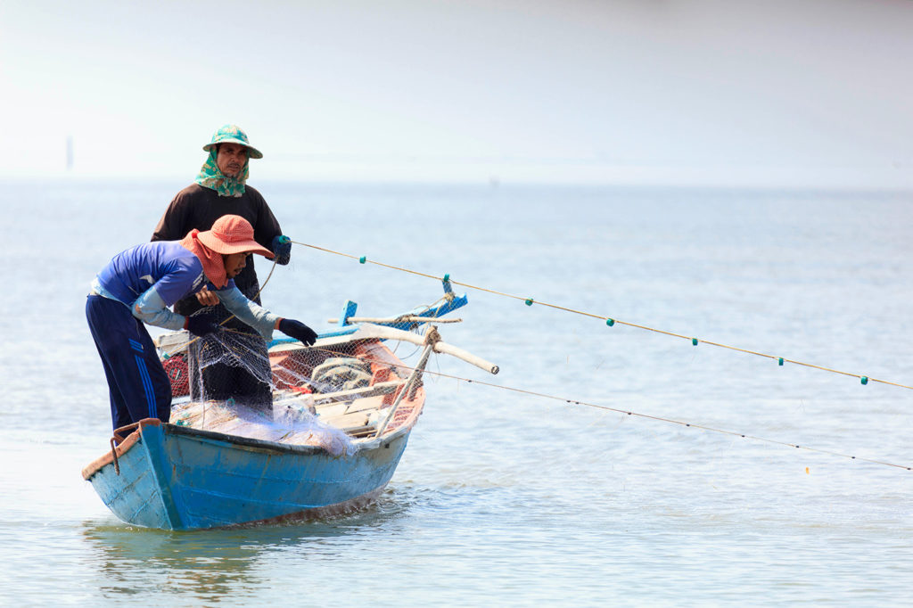 Fishermen with a cast net in the South China Sea, Kampot, Cambodia. Credit: John Michaels / Alamy Stock Photo. MFW9K3