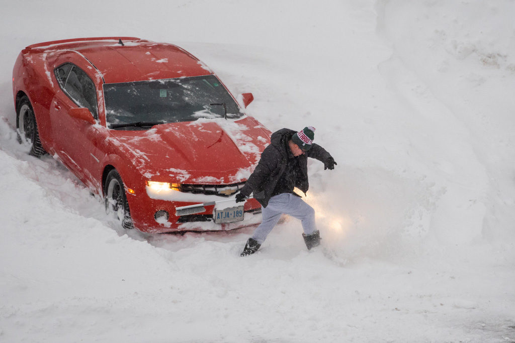 Toronto, Canada. 29th Jan 2019. A man digs out a red Chevrolet car from the parking lot snow in the morning