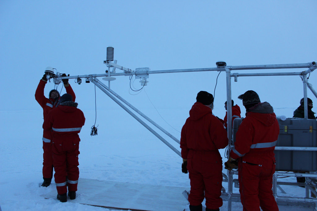 Dr Ola Perrson and other MOSAiC scientists set up a scientific instrument in the Central Arctic Ocean. Credit: Daisy Dunne for Carbon Brief