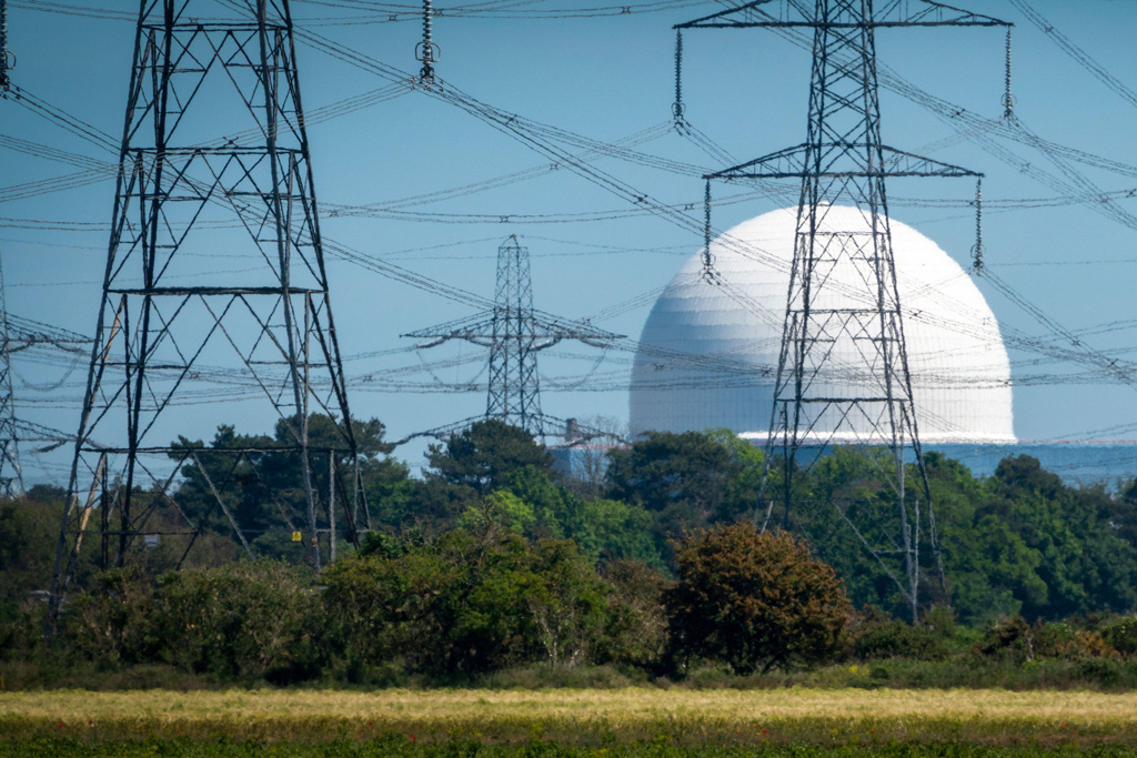 Sizewell B nuclear power plant with several electricity pylons in front seen through a distorting heat haze.